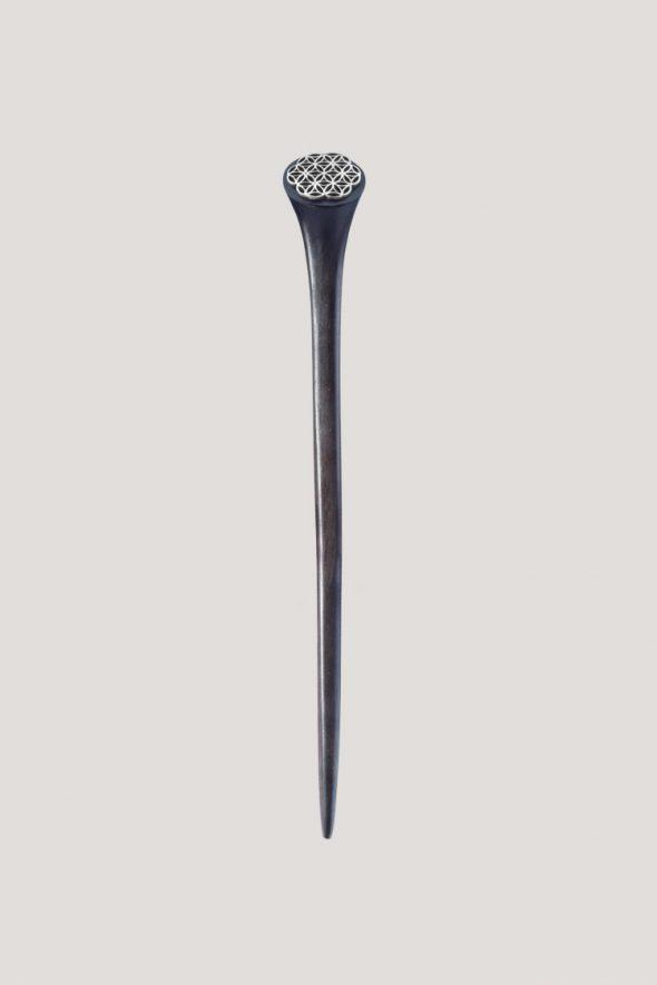 accesorio para el pelo, palo de madera de 16 cm de largo con una decoración en la punta que es en acero plateado y tiene la forma de la flor de la vida geometria sagrada